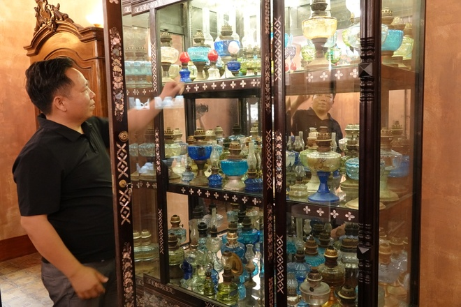 The oil lamps displayed by Mr. Cao Thanh Tuan in a beautiful old wooden cabinet /// Photo: DUY TAN