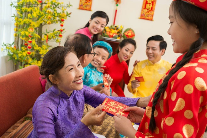 Adults give luckey money for children on Vietnamese New Year Day